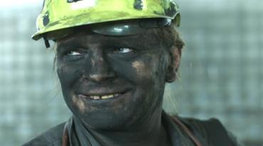 A close-up of a miner's face. His entire face is black from coal dust. He's wearing a yellow helmet and smiling. His white teeth are in sharp contrast to his dark face.