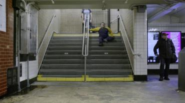 A two-way staircase is divided in half by a rail. On the right, an older, short-haired man is sitting on the third step down. A second person, whose head is not seen in the shot, waits for him at the top of the stairs.
