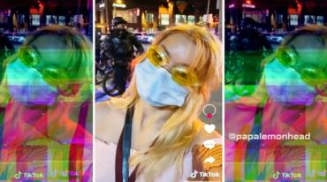 A neon-coloured blurry photo showing the face of a young woman in the forefront. She is on the street and there is a man on a motorcycle behind her. She is wearing yellow swimming goggles and a surgical mask.