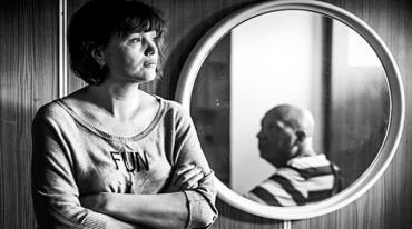 """A woman is standing with arms folded next to a round mirror. She is wearing a t-shirt that says """"FUN"""". She has a thoughtful expression. In the mirror we see the reflection of a bald man's head. He is wearing a striped t-shirt and looking towards the woman."""