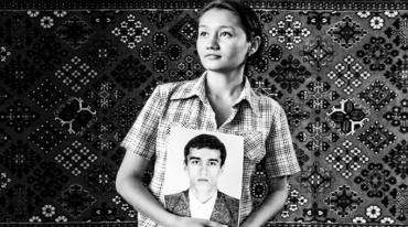A woman in a short-sleeved shirt stands in the foreground gazing with hope into the distance. She is holding a photo of a man who is wearing a suit and has an unreadable expression on his face. The backdrop is formed by woven fabric with a distinctive Oriental pattern.