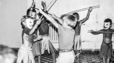 A group of seven randomly positioned children, dressed as Native Americans and wearing white masks, are playing with wooden sticks in a white room.