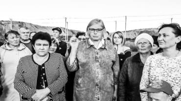 A group of middle-aged women are facing forward and looking into the camera. The one in the middle has distinctive spectacles and is talking towards the camera.She is gesticulating with one uplifted hand.