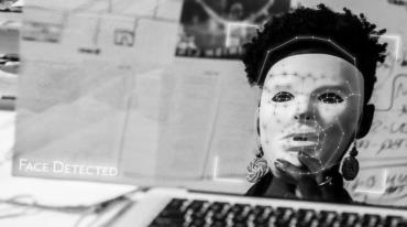 """View from the perspective of a computer algorithm. We see a black woman with a noticeable afro and large round earrings holding up a white mask to cover her face. There are several connected points on the white mask outlining the basic contours of the scanned face. In the corner we see the message """"Face detected."""""""