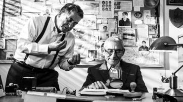 An elderly man in a suit and wearing glasses sits at a desk. He is smiling as he reads  an open notebook using a magnifying glass. There is a middle-aged man standing to his left, who is leaning over him and expressively gesticulating with his hands.