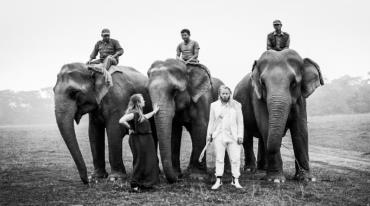 Three large elephants are standing in a meadow, each with a rider on its back. In the front, there is a woman standing to the left of the middle elephant petting its trunk, and there is a man with long blond hair and wearing a white suit standing between the middle elephant and the one furthest right.