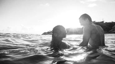A man and a woman swim in the sea. The setting sun is shining brightly into their eyes.