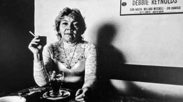 An older woman wearing a turtleneck decorated with lace at the top is sitting at a table, She is holding a cigarette and there is a glass of coffee in front of her. She is looking ahead with a fixed expression on her face.