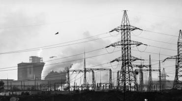 The scene is dominated by high-voltage power lines consisting of several tall pylon and many wires. An industrial building stands in the background, and thick white smoke rises out of its chimneys. The silhouette of a flying bird is visible above the wires.