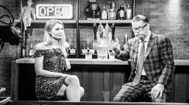 """A man and woman are sitting at a bar. Behind them we see a beer tap, bottles of alcohol on shelves, two puppets and a neon sign reading """"Open"""". The woman has long, soft blonde hair and is wearing a tight off-the-shoulder dress ending above her knees. It seems as if she is ignoring the man. The man is older and has slicked back hair. He is wearing a checked suit and glasses. He is looking towards the woman and has a lifted index finger."""