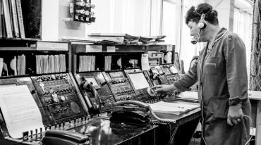 An older woman wearing blue coveralls and a headset stands next to an old-fashioned telephone switch board. She is reaching towards the number dial.
