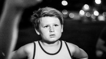 A small boy with short blond hair thoughtfully lookstoward the front. He is wearing a singlet and there are blurry lights visible in the distance behind him.