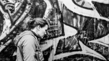 A woman with her curly blond hair tied back in a ponytail, stands in profile next to a wall covered with conspicuous graffiti.