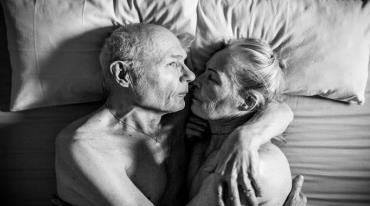 An elderly man and woman are embracing in bed.