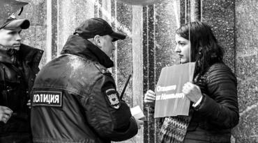 On the right, a young woman with her back to a building. She is holding a paper sign with something written in Cyrillic. On the left there are two policemen facing her, and one of them is talking to her from close to. All of them are wet from the rain.