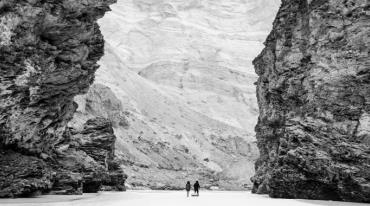 Two people, seen from somewhat afar, are walking through a gorge.
