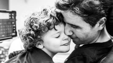 The close-up photo shows the faces of a man and a small child, both with their eyes closed, lovingly pressed together. The child has very curly hair. There is a glowing monitor screen or tablet in the background.