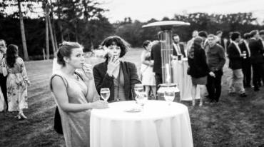 A garden party. Two young women are sitting at a round, cloth- covered table. Both of them have a cigarette in one hand and a glass of wine in the other. There is a group of people gathered in the background. Everyone is wearing party clothes.