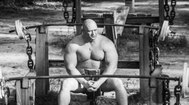 A large, heavily-muscled man, stripped to the waist, is sitting outside on an exercise machine. There are big barbells attached to the equipment by a large-linked chain both in front of and behind him.