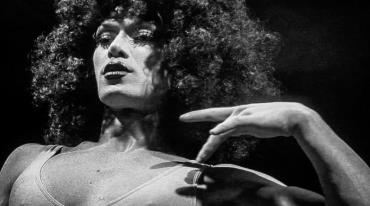 A headshot of a man dressed as a woman – a drag queen – who has expressive make-up and is wearing a curly wig. He has a serious, dreamy expression and is most probably in the middle of a performance.
