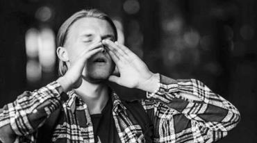 A young man with longish blonde hair is holding his hands cupped in front of his mouth to form an imaginary snout. His eyes are closed. It's obvious that he is imitating a wolf's howl.