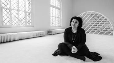 A woman dressed in black sits cross-legged on the floor in a white room. Her hands are folded in her lap and she is gazing ahead with a worried look on her face. There is a round spherical object made of bars in the back, and on the left there are radiators below large grated windows.