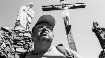 The film's protagonist Karel – a middle aged-man with chubby cheeks and wearing a baseball cap – is looking into the distance. Behind him we see a colourful, somewhat kitschy, sculpture of Christ on the cross, with a statue of the Virgin Mary on the left and another saint on the right.