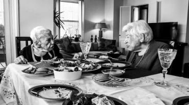 Two very elderly women are talking to each other at an abundantly set table.