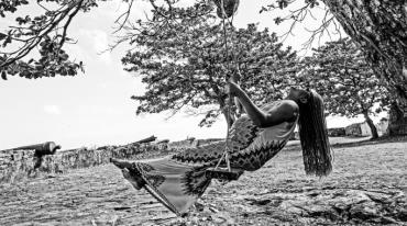 A pregnant woman with long braids who is barefoot and wearing a long patterned dress is swinging on a swing suspended from a tree. She leans back luxuriously as she swings forward. The surrounding landscape is rocky with several trees.