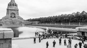 The photo is dominated by the colossal Monument to the Battle of the Nations in Leipzig, which reminds one of a grandiose grave. A group of people is standing in front of it waving the flags of the nations which once fell under Soviet influence, including the Czech flag.