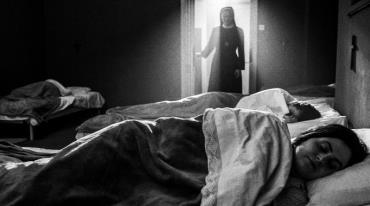 Four young girls are sleeping in four beds in a room. A nun is standing in the doorway watching them. Her figure is backlit by the ceiling light in the room behind her.