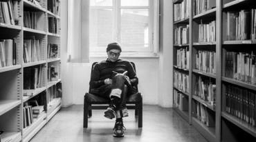 Facing the camera, a man is stting in an armchair, leggs crossed, reading a book. On both sides next to him, there are large, wall-to-wall bookshelfs, full of books. Behind the chair is a window.