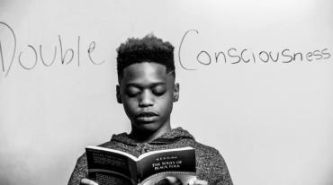 """A black boy with dark hair and wearing a sweatshirt is holding a book and concentrating on reading. Behind him we see the phrase """"Double Consciousness"""" handwritten on a white background."""
