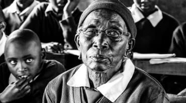 An elderly black African woman sits in the forefront, looking into the camera. Behind her, children are sitting at school desks.