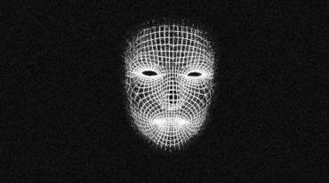 A computer-generated image of a white face emerges from a dark background. It consists of vertical and horizontal lines that form eyes, nose and mouth.