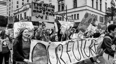 """A crowd of young people are marching down a city street. Most of them are chanting slogans and holding up signs. The largest of these, a banner reading """"OUR FUTURE"""", is carried by several people at the forefront."""