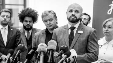 A press conference. A bearded bald man stands in the front. He is Czeslaw Walek, the leader of the We Are Fair coalition. He is wearing a suit and there are several microphones in front of him. There are a number of other people – politicians – standing next to him and behind him.