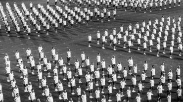 Dozens of people grouped in several precise square formations are standing on a grassy green field. They are wearing white t-shirts and blue shorts. They are Sokols ready to exercise.