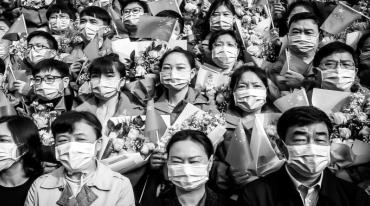 About 20 faces are staring at the camera. They are Asians, they were surgical masks over their mouths and noses. They stand close together in rows, men and women mixed. Each of them holds a bouquet of flowers wrapped in paper in their left hand and a Chinese flag in their right. Some wave the flag, most look very serious.