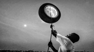 A man is carrying a burning tyre attached to a long pole he holds above his head.