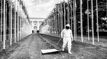 In the forefront we see a person wearing a protective suit and helmet dragging a piece of white canvas attached to a pole over the grass. There are rows of flagpoles with many flags along the sides and an imposing building in the back.