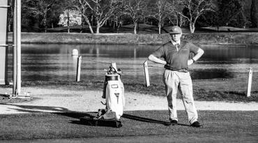 An older man wearing a polo shirt and baseball cap stands with hands on hips on a mown lawn. He has an obstinate look on his face. A set of golf clubs stands at the ready to his left, and behind him there is a body of water.