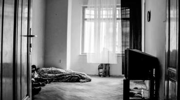 A person is standing at the window in a basic housing unit and looking out. They are not fully visible as they are behind the curtain. The room contains nothing other than an old television set and some bedding on the floor, in which the flat's other occupant is bundled.