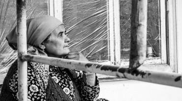 An older woman with a headscarf and wearing a flowered blouse is shown in profile as she looks ahead. Behind her there is a triple-pane window, and in front of her, to her right, a section of railing.