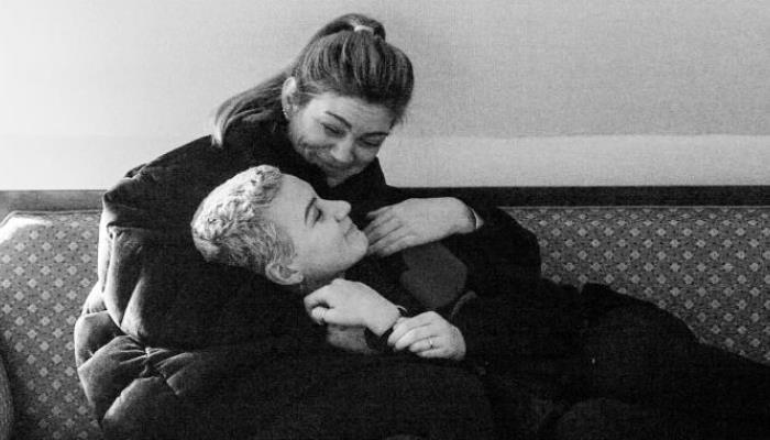 Na gauči sedí dlouhovlasá brunetka ve středním věku a v náručí jí leží mladá, na krátko ostříhaná a na blond obarvená dívka. Obě se tváří spokojeně.