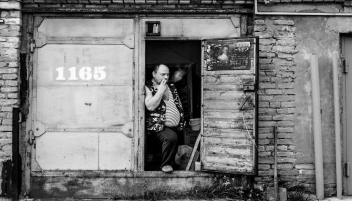 """A balding man with a cigarette in his mouth is standing in the right hand side doorway of a garage with two doors. He is wearing a striped t-shirt that is tight across his belly, and a camouflage pattern waistcoat. One of his feet is resting on the threshold. He looks grumpy. The number """"1165"""" is written on the left garage door."""