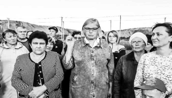 Několik žen středního věku stojí a hledí přímo do záběru. Prostřední z nich má výrazné brýle a mluví směrem do kamery. Gestikuluje zvednutou rukou.