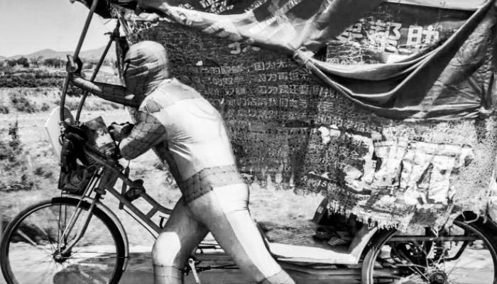 A man in a Spiderman costume pushes a tricycle carrying textile banners with Chinese writing.