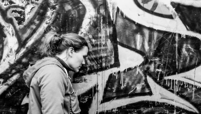 Žena s kudrnatými blond vlasy v culíku stojí z pofilu vedle výraznými graffiti pomalované zdi.