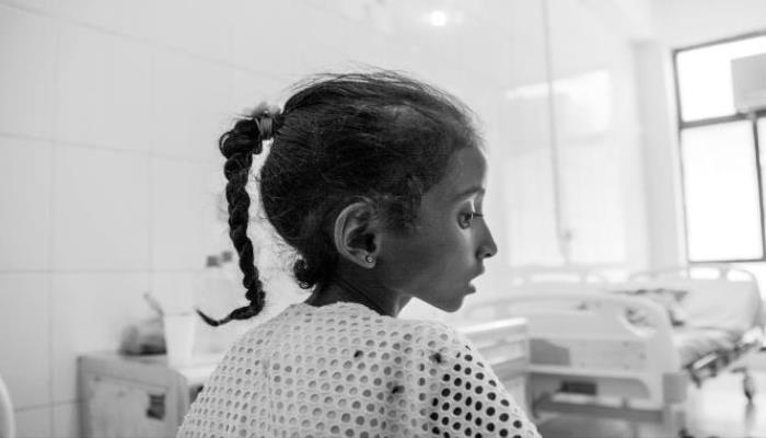 Drobná dívka sedí v prázdném nemocničním pokoji, je zabrána z profilu. Je velmi hubená, má výrazné oči a vlasy spletené do copánku.